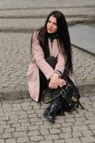 Модель показывает одежды осени сидя на тротуаре Стоковое Фото