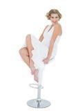 Модель счастливой моды белокурая представляя сидеть на стуле адвокатского сословия стоковая фотография rf