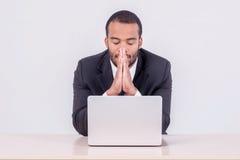 Молитва на работе Усмехаясь африканский бизнесмен сидя на столе дальше Стоковые Фотографии RF