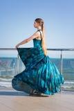 Модная девушка в платье бирюзы на яркой голубой предпосылке моря Дама остается на балконе стекла ` s гостиницы Стоковая Фотография RF