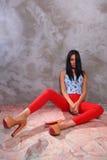 Модная девушка в ярких одеждах сидит на серой предпосылке стены Стоковая Фотография RF
