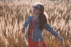 Модная девушка на поле в солнце излучает Стоковое Изображение RF