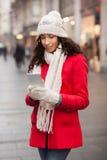 Модная женщина в красной крышке пальто и шерстей и перчатки с smartphone в Хане Стоковые Фото