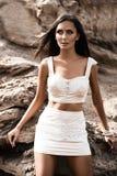 Модная женщина представляя на пляже с утесами в платье стоковые фото