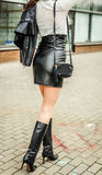 Модная современная сексуальная девушка в юбке черной кожи на высокой талии и высоких ботинок на пятке представляя на улице Стоковое Фото