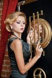 Модная чувственная привлекательная дама при черное платье стоя около сейфа в винтажной сцене Женщина блондинкы коротких волос Стоковая Фотография