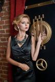 Модная чувственная привлекательная дама при черное платье стоя около сейфа в винтажной сцене Женщина блондинкы коротких волос Стоковое Изображение