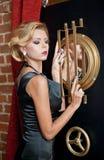 Модная чувственная привлекательная дама при черное платье стоя около сейфа в винтажной сцене Женщина блондинкы коротких волос Стоковая Фотография RF