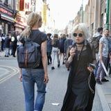 Модно одетая белокурая девушка в солнечных очках в черной тунике идя вдоль Brickline стоковое фото