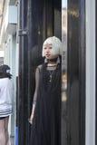 Модно одетая белокурая девушка в солнечных очках в черной тунике идя вдоль Brickline стоковое изображение