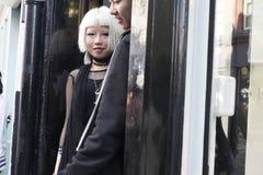 Модно одетая белокурая девушка в солнечных очках в черной тунике идя вдоль Brickline стоковое изображение rf