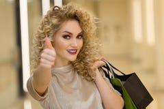 Модно одетая женщина при хозяйственные сумки показывая большие пальцы руки вверх в моле стоковое фото
