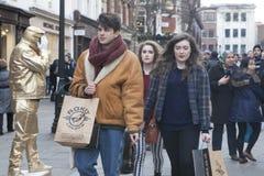 Модно одетое молодые люди идет ходить по магазинам на Ковент Гардене Куртка молодого человека нося кожаная бежевая с большим шарф стоковая фотография rf