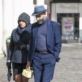 Модно одетые человек и женщина в голубых костюмах и шляпах идут вниз с улицы стоковое изображение