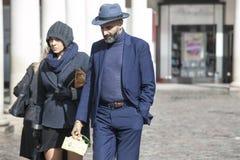 Модно одетые человек и женщина в голубых костюмах и шляпах идут вниз с улицы стоковое изображение rf
