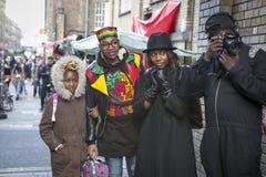 Модно одетые люди слушая к музыкантам улицы на майне кирпича стоковое изображение