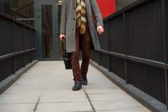 Модно одетый бизнесмен идет от офисного здания с сумкой в его руке стоковые изображения rf