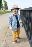Модно одетый мальчик в соломенной шляпе идет в лето стоковая фотография rf