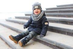 Модно одетый мальчик сидя на лестницах outdoors в spr стоковое изображение rf
