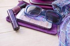 Модные женские аксессуары наблюдают муфту и мобильный телефон губной помады солнечных очков фиолетовые женщина красных s красотки Стоковое Фото