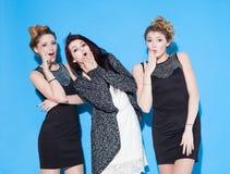 Модные красивые молодые подруги стоя совместно около голубой предпосылки 2 блондинкы и брюнет Иметь смешное и pos Стоковые Изображения