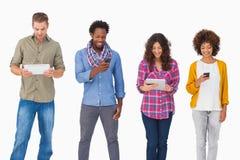 Модные друзья стоя в ряд используя приборы средств массовой информации стоковые изображения rf