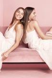 Модные сестры близнецов представляя на розовой предпосылке Стоковая Фотография