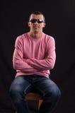 Модный молодой парень в солнечных очках сидя в стуле стоковое изображение rf