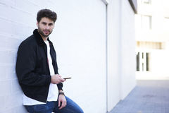 Модный парень в светлых джинсах, белой футболке и темной куртке Стоковое Фото
