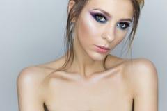 Модный портрет красивой сексуальной девушки с шальным стилем причёсок с ярким покрашенным составом с оголенными плечами в студии  Стоковая Фотография