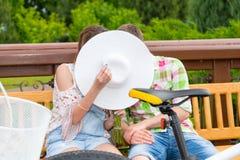 Модный прятать человека и женщины целуя за шляпой Стоковое фото RF