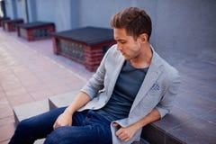 Модный человек волос брюнет сидя на шагах Стоковые Изображения RF