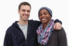 2 модных друз смотря камеру и усмехаться Стоковая Фотография