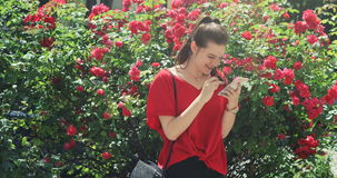 Моложавая милая девушка празднуя счастливые новости от ее smartphone phablet акции видеоматериалы