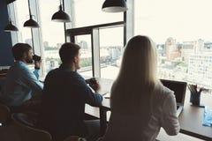 Моложавые мужчины и дама имея перерыв на чашку кофе пока работа крытая Стоковые Изображения