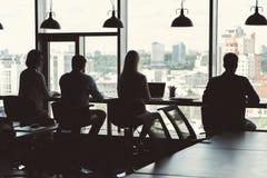 4 моложавых парни и дамы работая в большой комнате офиса Стоковые Фотографии RF