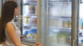 Молокозавод молодой женщины покупая или refrigerated бакалеи на супермаркете в refrigerated двери раздела раскрывая стеклянной де акции видеоматериалы
