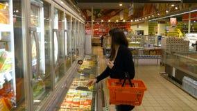 Молокозавод молодой женщины покупая или refrigerated бакалеи на супермаркете акции видеоматериалы