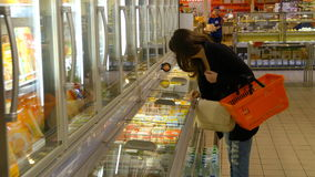 Молокозавод молодой женщины покупая или refrigerated бакалеи на супермаркете видеоматериал