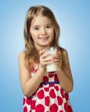 Молоко владением питья девушки ребенка стеклянное изолированное на голубой предпосылке Стоковое Изображение RF