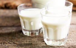 Молоко в стеклах, винтажная деревянная предпосылка козы, селективный фокус Стоковые Изображения RF