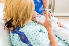 Молоко женщины подавая к Newborn Babygirl на больнице Стоковые Изображения RF