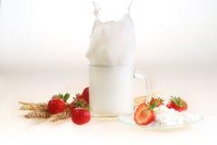 Молоко и клубника на белой предпосылке, выплеск молока в tran Стоковое Изображение