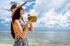 Молоко кокоса женщины туристское выпивая на пляже в праздниках Стоковая Фотография
