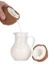 Молоко кокоса руки женщины лить в опарник изолированный на белизне стоковая фотография rf