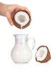 Молоко кокоса руки женщины лить в опарник на белизне стоковое фото rf