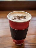 Молоко кофе в бумажном стаканчике на таблице Стоковая Фотография