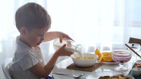 Молоко мальчика лить в шар хлопьев мозоли Мальчик варит завтрак сток-видео