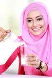 Молоко молодой мусульманской женщины лить в стекло стоковая фотография rf