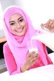 Молоко молодой мусульманской женщины лить в стекло стоковые изображения rf
